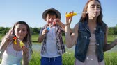 satisfeito : childrens fun, emotional sisters with small boy in Hat blowing soap bubbles on meadow near lake against blue sky in summer