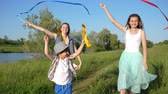 ecstatic : amused teenager girls with kid have fun and waving with colored ribbons outdoors near lough