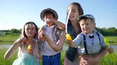 soap bubbles : emotional family with soap bubbles rest on meadow near river against blue sky
