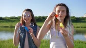 ecstatic : joyful girls adolescent make soap bubbles at nature near river Stock Footage