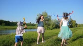 ecstatic : laughing children running and waving with colored ribbons on nature near river in summer