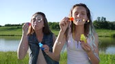 ecstatic : sincere emotions of teen girlfriends with soap bubbles in open air near loch Stock Footage