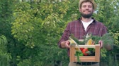 patlıcan : fall harvest, happy farmer in straw hat holds in hands wooden box with fresh vegetables at the garden