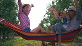függőágy : holiday home, happy parents with child on hammock in a apple garden have funs and enjoying nature in straw hats at warm summer day