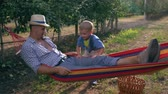 függőágy : outdoor recreation, child shakes his father in the hammock between rows of trees at the apple garden Stock mozgókép