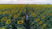 helianthus : happy smiling girl enjoying nature and runs between rows of yellow sunflowers on field at summer