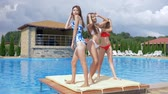 dinlenmek : cheerful holidays, girls have fun and dance near blue pool on the summer terrace in sexy swimsuits