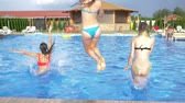 traseiro : jump into water, young girls in swimsuits running in swimming pool at hot summer days