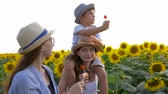 lolipop : cheerful children eating sweet candy on a stick during a walk in the wonderful yellow field with sunflowers in sunny light