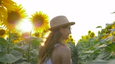 helianthus : nature, teenager walking on field of flowering sunflowers wearing glasses and a straw hat