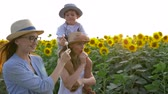 helianthus : rural, happy girls with little boy eating sweet lollipops on wonderful yellow field with sunflowers