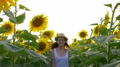 helianthus : smiling girl teenager wearing glasses and a straw hat walking through a field of flowering sunflowers