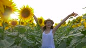 helianthus : teenager girl walk around the field with sunflowers and enjoy the fresh air in slow motion Stock Footage