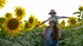 helianthus : village summer vacation, teenager girl carrys boy on neck and walks across the field with sunflowers in the backlight