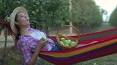 hozam : rest in garden, happy country girl lies in hammock and eats apples on nature during harvesting