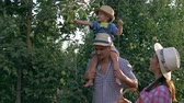 working parents : rural childhood, young farmers with son harvesting apples at orchard in autumn