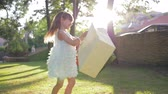šatník : Laughing little girl shopper enjoys new purchases in paper bags and is rotates with happiness at sunny park after visiting fashion stores Dostupné videozáznamy