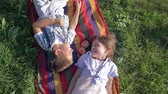 deka : cheerful kids on nature laugh and lying on a plaid with apples on green grass