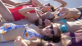 eğlenmek : pool party, joyful girls with beautiful figures in swimsuits waving hands hi lying on deckchair near Poolside close-up on summer vacation Stok Video