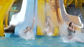 plunge : aquapark, cheerful Friends girls sliding on water slide and Dives into Poolside with Splashing on summer vacation