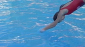 plavky : young woman in swimsuit jumping into clean blue pool and disappears under water close-up