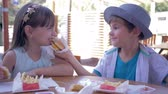lánytestvér : junk food, cute child boy feeding girlfriend burger in Street Cafe close-up Stock mozgókép