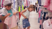 lánytestvér : children on shopping, little buyers choose new fashionable clothes at expensive boutique during seasonal sale