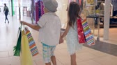 бутик : children on shopping, stylish child friends with purchases into hands going by shop windows at mall after buy in expensive boutiques on weekends