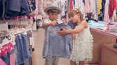 weekdays : shopping holiday, little friends choose new stylish garments in fashion shop during seasonal discounts Stock Footage