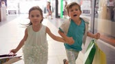 sexta feira : joyful children with shopping bags run to make purchases at discounts during sales on black Friday at mall