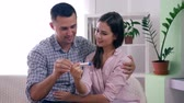 doğurganlık : healthy family couple with pregnancy test happy with positive result and happily hugging each other in room at home close-up Stok Video