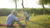 kruiwagen : happy family idyll, father shows one, two, three and then catches the running son into hands and they fall on blanket in bright sunlight Stockvideo