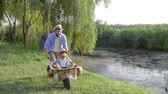 kruiwagen : happy family vacation in countryside, father fools around with his son in a wheelbarrow near river with reeds Stockvideo