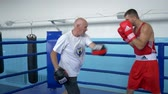 pugilist : KHERSON, UKRAINE - SEPTEMBER 3, 2018: athletic man in boxing gloves working out on technique of beats fists while training with old coach on ring at sports studio