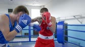 pugilist : KHERSON, UKRAINE - SEPTEMBER 3, 2018: Kickboxing, Men athletes practice technique of boxer strikes on training before match in ring at sports studio