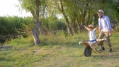 kruiwagen : cheerful family vacation on nature, dad carries a joyful child boy in a wheelbarrow in slow motion