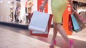 bright clothes : legs of shopaholics girl in stylish bright shoes with shopping bags are walking along mall in season of discounts Stock Footage