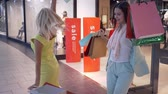 買い物客 : happy shopper women friends dance after shopping at discounts into expensive stores in sales season at mall