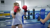 pugilist : sport and people, two young women exercising and fighting on boxing ring in gym Stock Footage