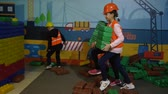 colete : KIEV, UKRAINE - OCTOBER 18, 2018: children professions, kids in yellow helmets and vests play with the building constructor Vídeos