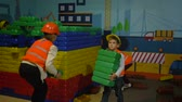 vesta : KIEV, UKRAINE - OCTOBER 18, 2018: kids playing in profession on construction site, small builders in a helmets and vests play with the constructor