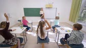 maličký : group of schoolkids raise hands to answer at lesson while sitting at desk in front of teacher to board in elementary school class Dostupné videozáznamy