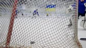 drible : KHERSON, UKRAINE - OCTOBER 17, 2018: goalkeeper in hockey suit stands at gate and catches puck from opponent at ice rink during competition, goal close-up