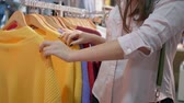 bright clothes : shopper lifestyle, customers girl hands are choosing fashionable new clothes in boutique close up during seasonal discounts