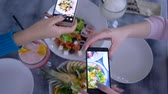 doğru : blogging, smartphone in hand girlfriends makes photo of useful vegetarian food during breakfast for social media in restaurant, close up on unfocused background Stok Video