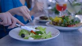 snellente : healthy diet lunch, hands closeup eating vegetable useful salad from plate during food time in restaurant close-up