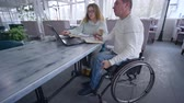 inválido : freelance businessman is disabled on wheelchair with woman using smart computer technology for developing and planning business ideas in restaurant Vídeos