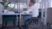 cadeira de rodas : handicapped man in wheel chair talking on a mobile phone and working with a computer laptop sitting at a table with cup of coffee in a restaurant.