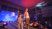 подиум : KHERSON, UKRAINE - DECEMBER 01, 2018: stylish Catwalk model with kid girl go on podium on presentation show of designer clothes at fashion evening