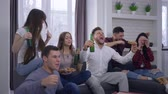 kiabálás : emotion, fans watching football match on TV with excitement and then rejoice at the victory sitting on the couch with a beverages and pizza at home